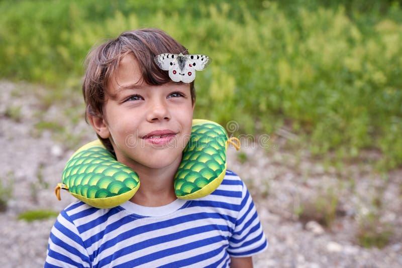 Un enfant dans un T-shirt rayé avec un grand papillon sur sa tête dans la perspective d'herbe image stock