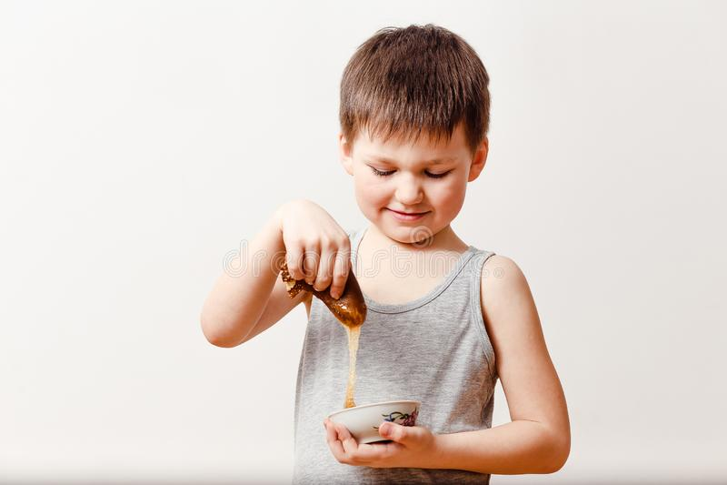 Un enfant de cinq ans enduit une crêpe roulée de beurre du miel sur un fond blanc Vacances russes et enfants de Maslenitsa photos stock