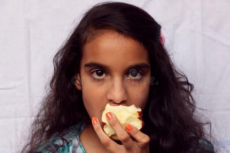 Un enfant de fille mangeant la pomme image stock