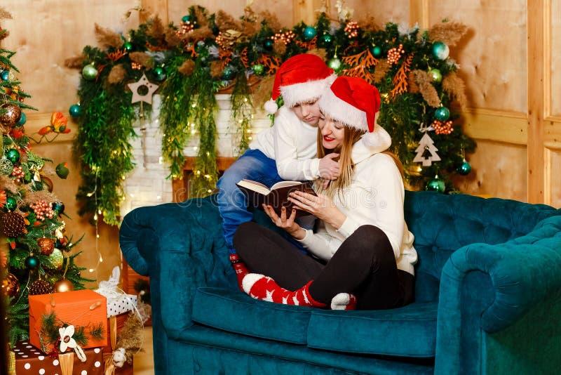 Un enfant de sept ans étreint sa mère à Noël Mère et fils dans des chandails beiges image libre de droits