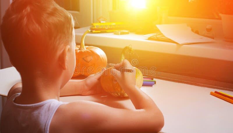 Un enfant dessine un visage sur un potiron photographie stock