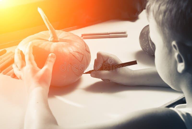 Un enfant dessine un visage sur un potiron images libres de droits