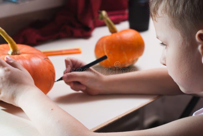 Un enfant dessine un visage sur un potiron image stock
