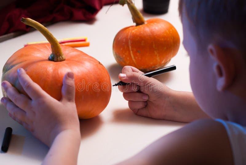 Un enfant dessine un visage sur un potiron image libre de droits