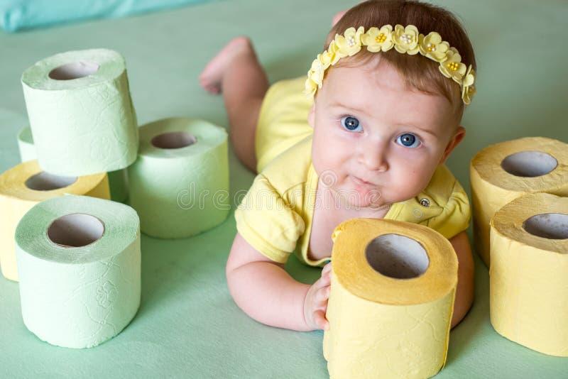 Un enfant en bas âge déchirant le papier hygiénique dans le studio de salle de bains photos libres de droits