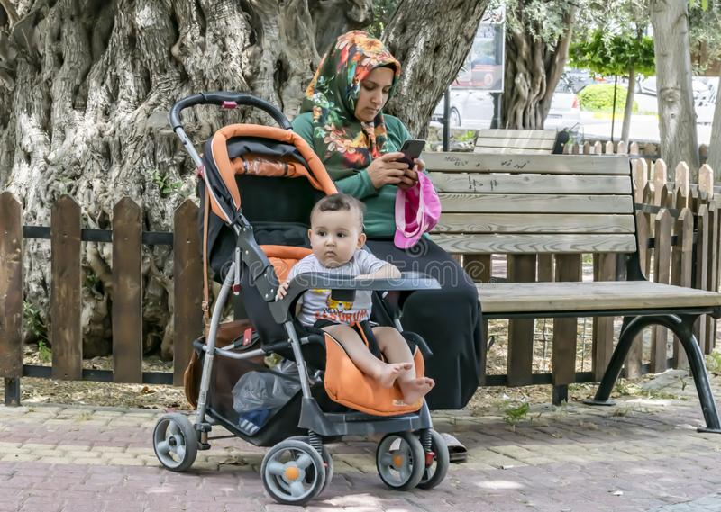 Un enfant a ennuyé la séance dans une poussette de bébé Une mère féminine habillée dans l'habillement musulman traditionnel utili images libres de droits