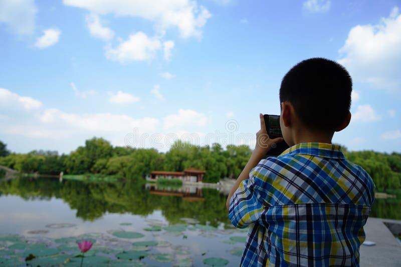 Un enfant est concentré sur prendre des photoes avec des fleurs de lotus photo stock