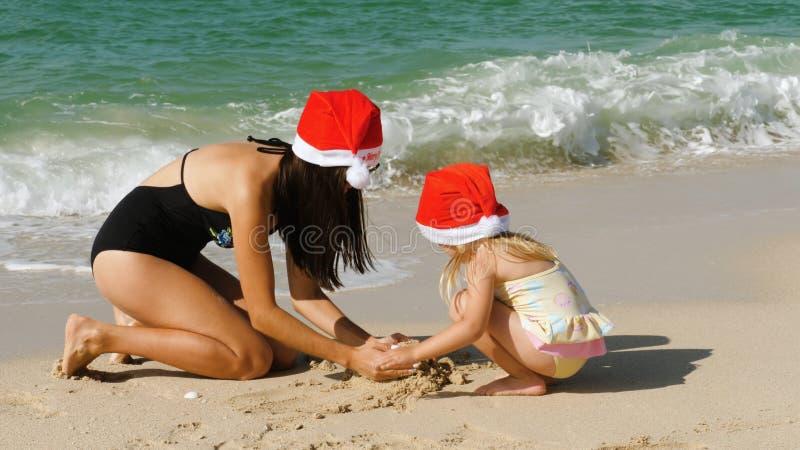 Un enfant et une mère utilisant un chapeau de Santa Claus sur la plage images libres de droits