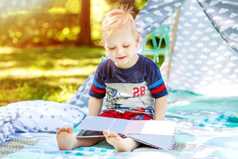 Un enfant heureux lit un livre en parc École maternelle de garçon Été T photo libre de droits