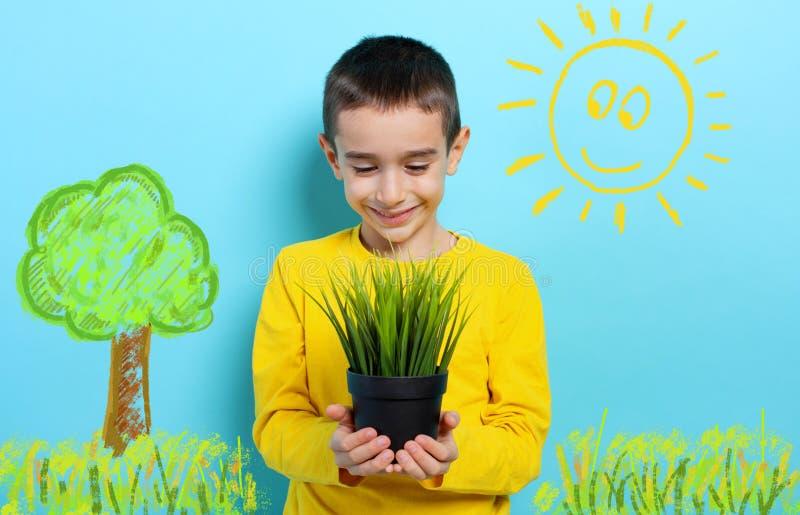 Un enfant heureux tient un petit arbre prêt à être planté Concept de boisement photos libres de droits
