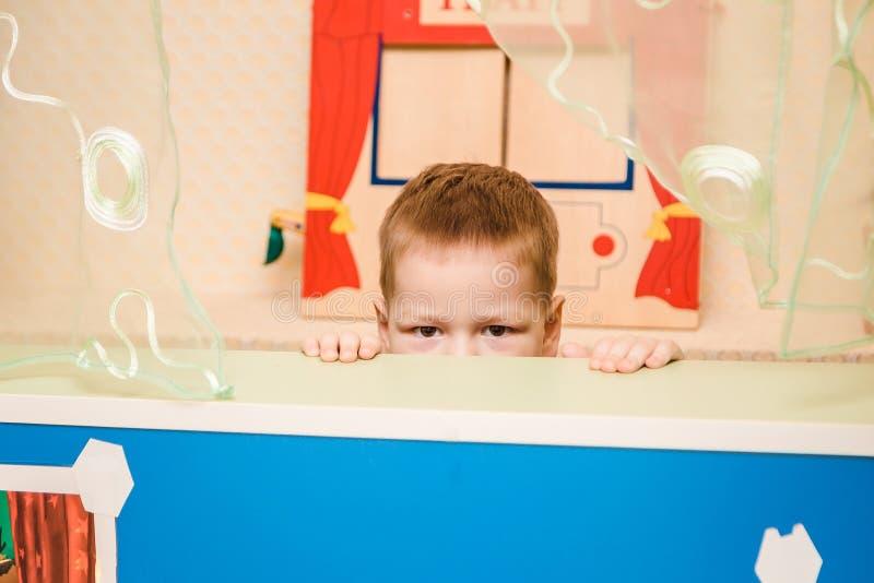 Un enfant jette un coup d'oeil par derrière une maison dans le jardin d'enfants photographie stock