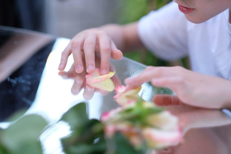 Un enfant jouant avec des pétales de rose photo libre de droits