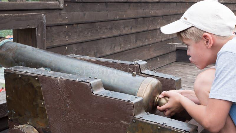 Un enfant jouant avec une vieille arme à feu sur le bateau photos libres de droits