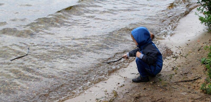 Un enfant jouant sur un rivage de lac photographie stock