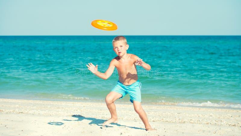 Un enfant joue avec un frisbee sur la plage photos stock