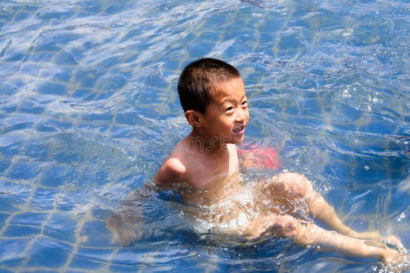 Un enfant joue heureusement dans l'eau photo stock
