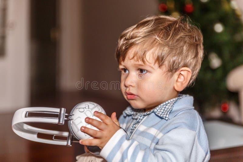 Un enfant mignon est prêt à écouter la musique avec un grand casque tandis que dans le salon photographie stock
