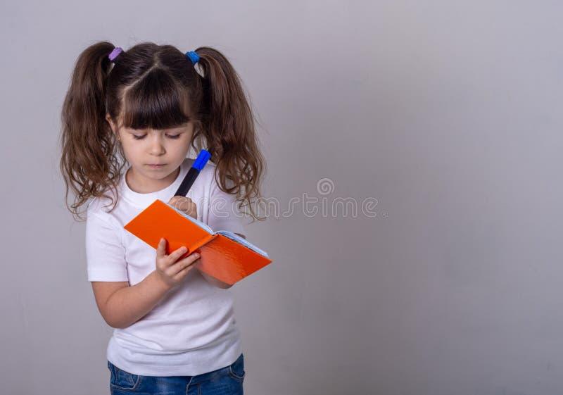 Un enfant mignon surpris écrivant dans un carnet avec un crayon, en gardant la bouche ouverte Enfant de 4 ou 5 ans, isolé images stock