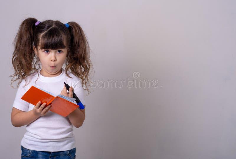 Un enfant mignon surpris écrivant dans un carnet avec un crayon, en gardant la bouche ouverte Enfant de 4 ou 5 ans, isolé photographie stock