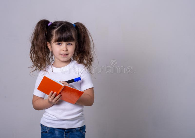 Un enfant mignon surpris écrivant dans un carnet avec un crayon, en gardant la bouche ouverte Enfant de 4 ou 5 ans, isolé photo stock