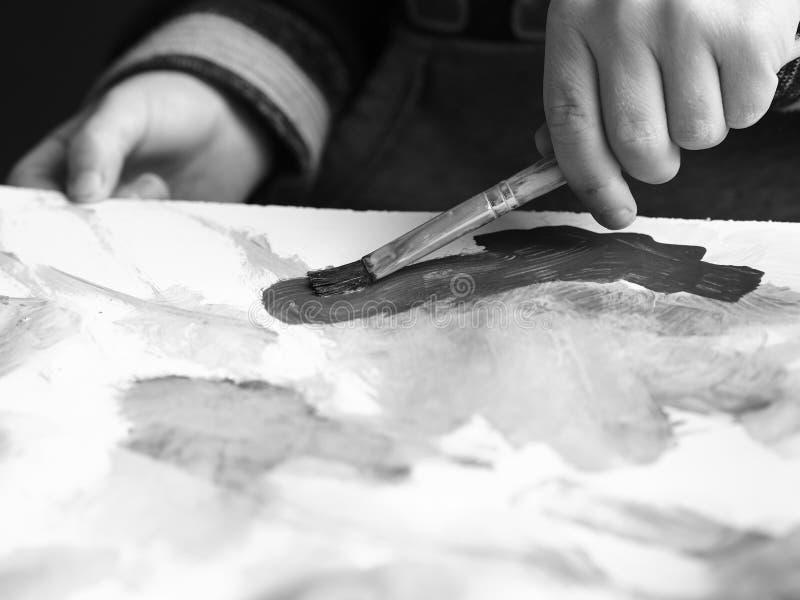 Un enfant peint un tableau avec une brosse et une aquarelle, image noire et blanche photographie stock