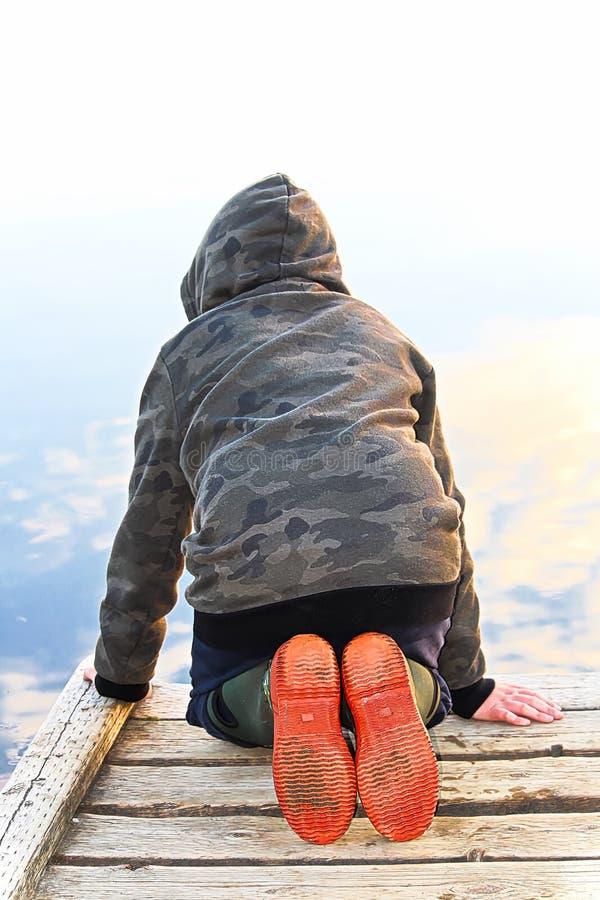 Un enfant regardant dans l'eau avec une réflexion de miroir du ciel image stock