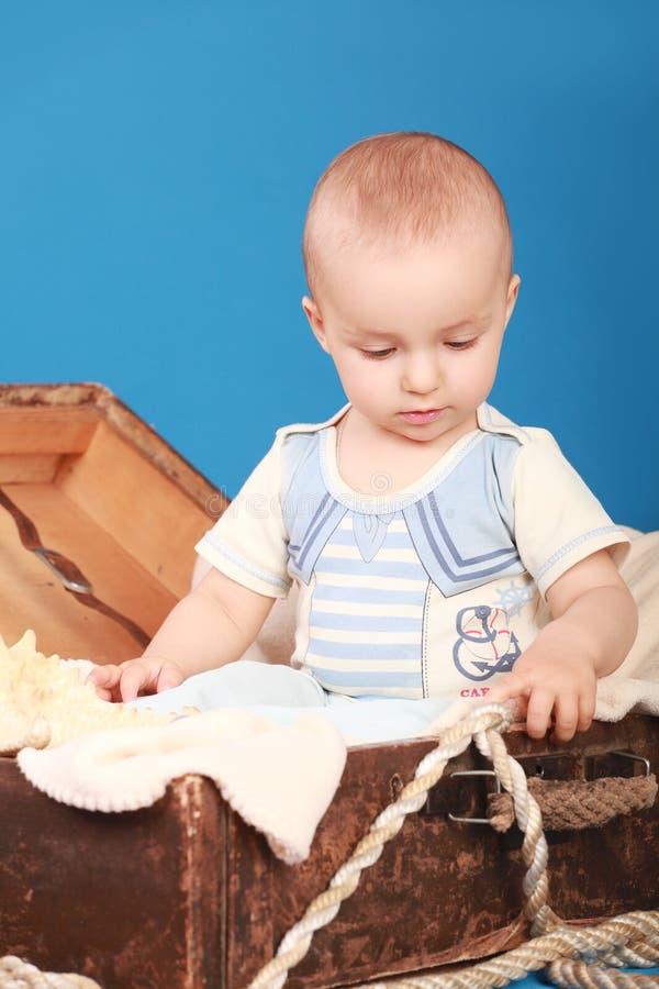 Un enfant s'assied dans un coffre dans un costume de marin et regarde la corde photo stock