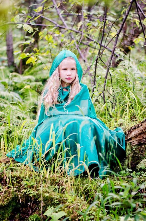 Un enfant s'assied parmi la forêt dans une robe verte avec le capot photos libres de droits