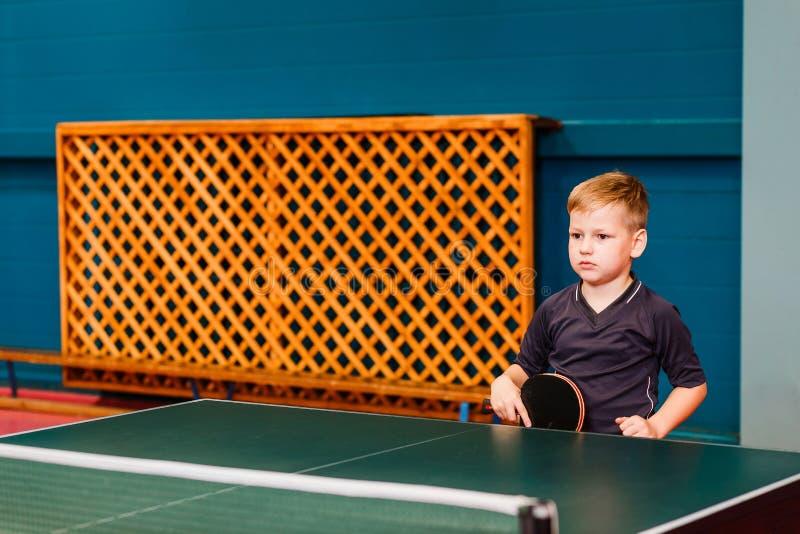 Un enfant se tient près de la raquette de tennis avec des mains photo stock