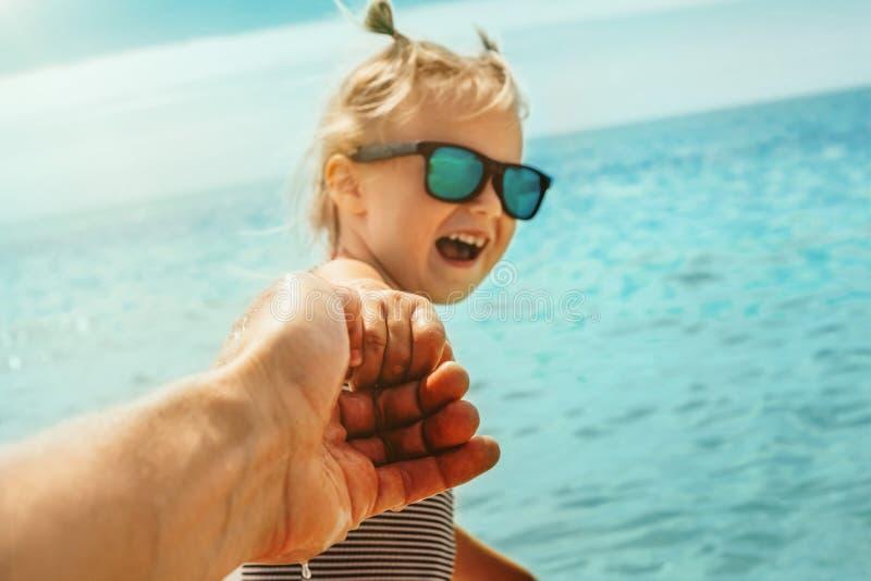 Un enfant tire le père pour nager en mer photos libres de droits