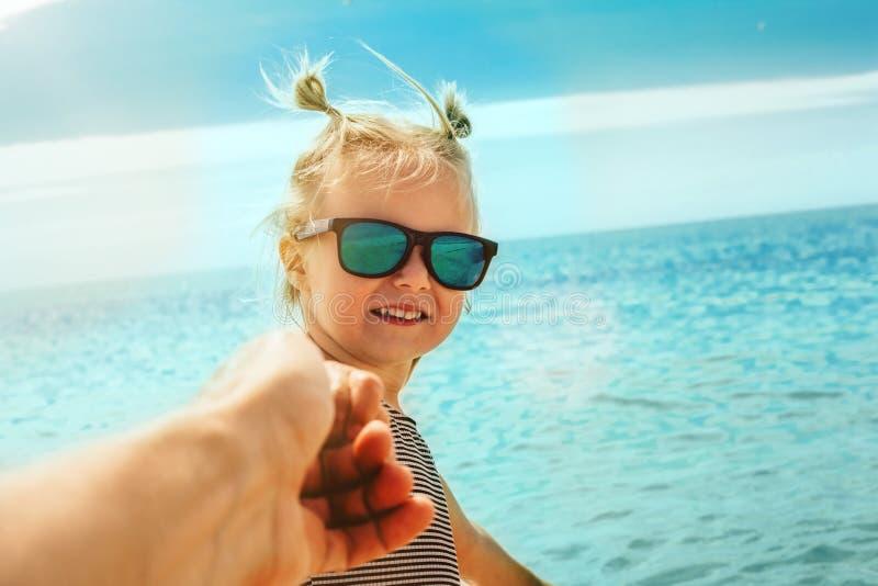 Un enfant tire le père pour nager en mer image libre de droits