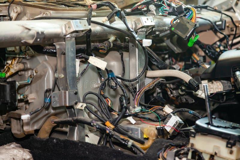 Un enredo grande de los alambres multicolores del enmarañamiento del cableado del coche miente en la cabina del coche desmontado  fotografía de archivo