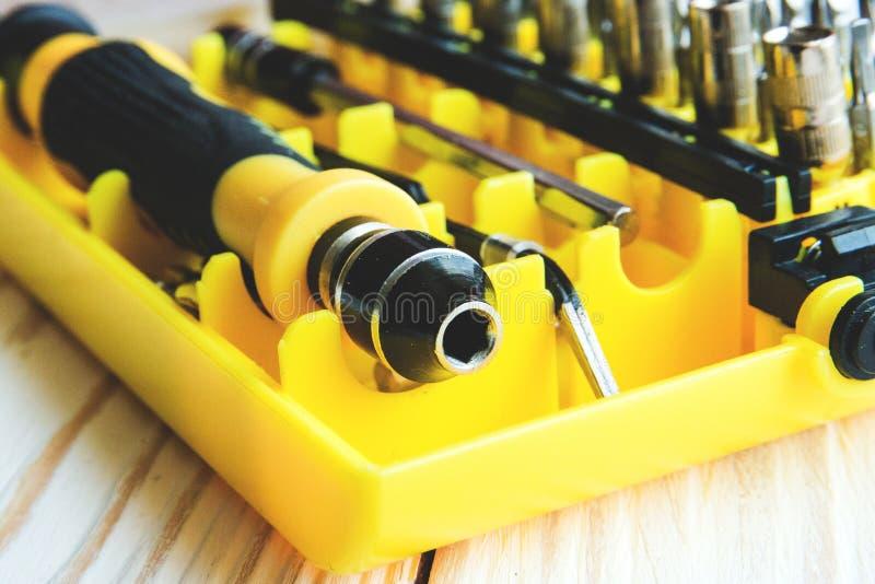 Un ensemble de becs de différentes tailles pour le plan rapproché de tournevis dans une boîte jaune, boîte à outils du ` s de pap photo stock