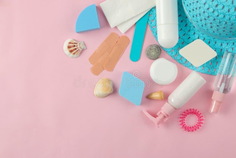 Un ensemble de cosmétiques et de produits de soin personnel pour le voyage et un chapeau sur un fond rose doux Principal v photo stock