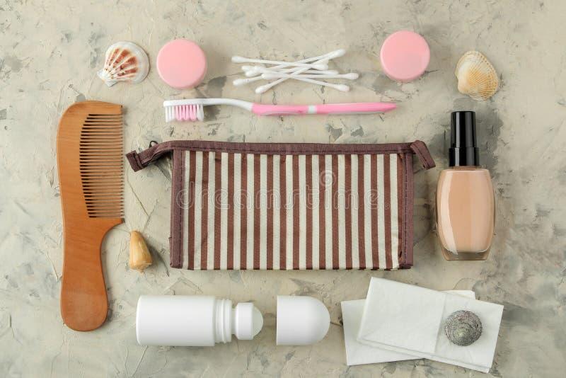 Un ensemble de cosmétiques et de produits de soin personnel pour le voyage dans un sac cosmétique sur un fond de ciment Vue sup?r photos stock