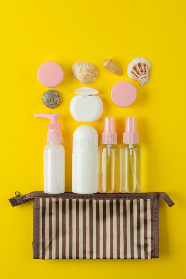 Un ensemble de cosmétiques et de produits de soin personnel pour le voyage dans un sac cosmétique sur un fond jaune lumineux Vue  photographie stock libre de droits