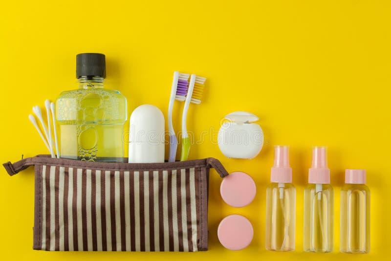 Un ensemble de cosmétiques et de produits de soin personnel pour le voyage dans un sac cosmétique sur un fond jaune lumineux Vue  photographie stock