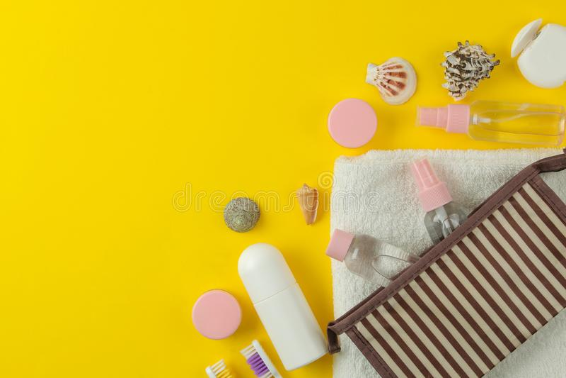 Un ensemble de cosmétiques et de produits de soin personnel pour le voyage dans un sac cosmétique sur un fond jaune lumineux Vue  images stock
