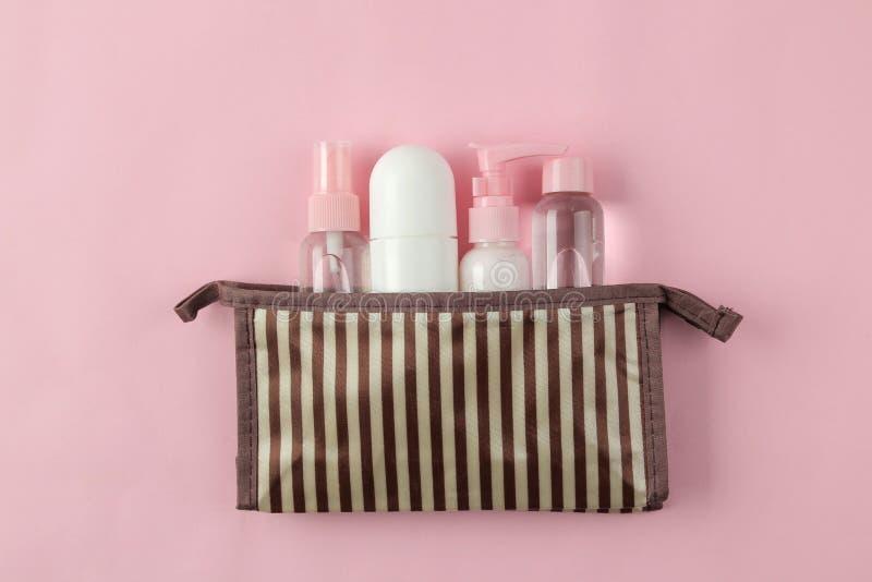 Un ensemble de cosmétiques et de produits de soin personnel pour le voyage dans un sac cosmétique sur un fond rose-clair Vue sup? images libres de droits