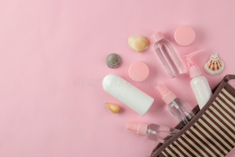 Un ensemble de cosmétiques et de produits de soin personnel pour le voyage dans un sac cosmétique sur un fond rose-clair Vue sup? images stock