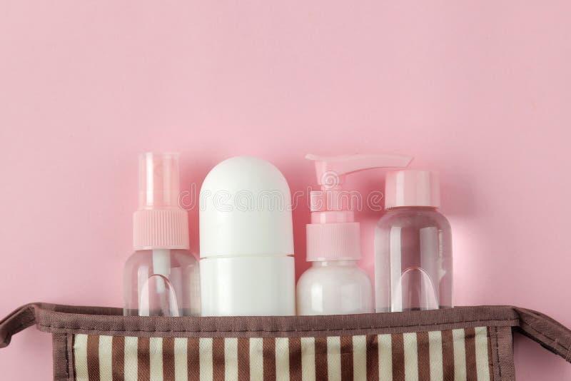 Un ensemble de cosmétiques et de produits de soin personnel pour le voyage dans un sac cosmétique sur un fond rose-clair Vue sup? image stock