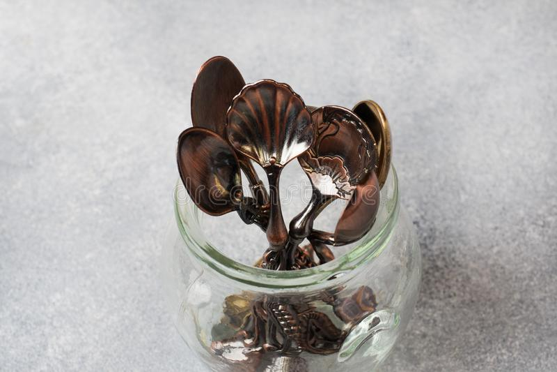 Un ensemble de différentes cuillères à café dans un pot en verre Fond gris avec l'espace de copie photos libres de droits