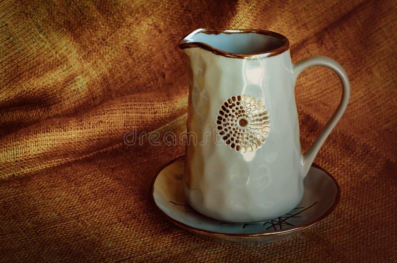 Un ensemble de plats en c?ramique Cruche et plat brillants bleus sur le tissu naturel Art de poterie Type rustique photo stock