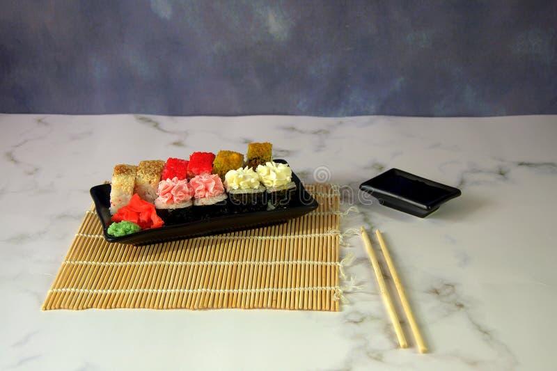 Un ensemble de sushi d'un plat noir en céramique, une tasse de sauces et les baguettes se trouvent sur une serviette en bambou Pl photographie stock