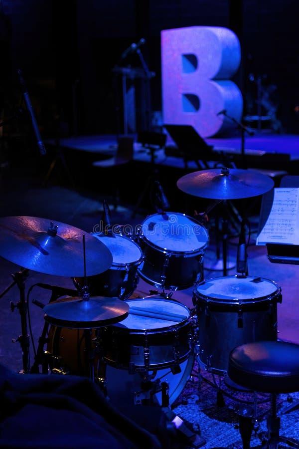 Un ensemble de tambours sur une étape, trempé dans la lumière bleu-clair images stock
