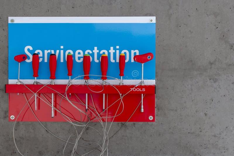 Un ensemble de tournevis avec les supports rouges et un ensemble sur un fond bleu et rouge avec la station service d'inscription photographie stock