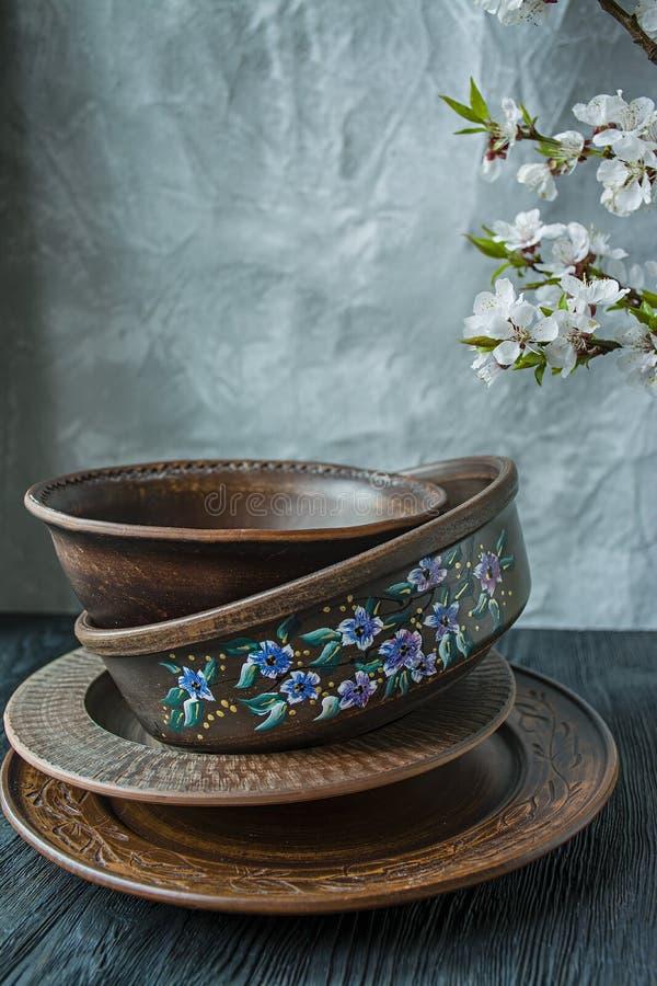 Un ensemble de vieille vaisselle en céramique Un ensemble de plats, cuvettes Une branche des abricots Fond en bois fonc? images stock