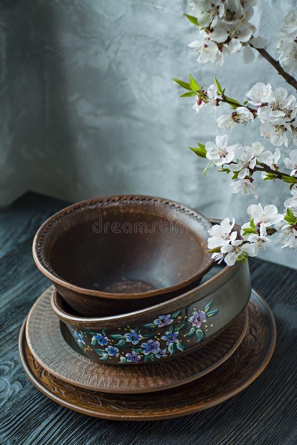 Un ensemble de vieille vaisselle en c?ramique Un ensemble de plats, cuvettes Une branche des abricots Fond en bois fonc? image libre de droits