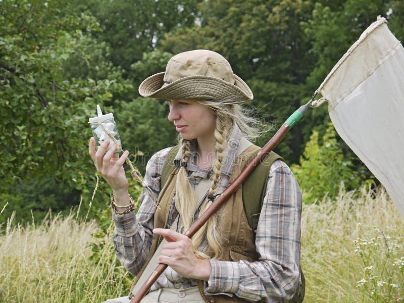 Un entomologo della giovane donna si è vestito in stile country, con una rete dell'insetto e una bottiglia di uccisione immagine stock