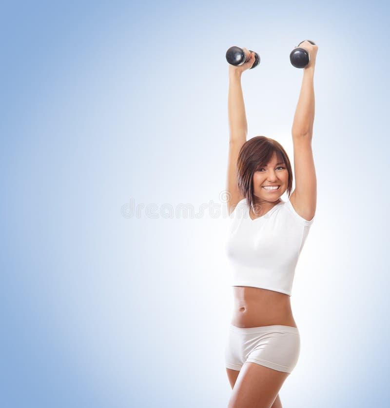 Un entrenamiento trigueno de los jóvenes y del ajuste con pesas de gimnasia fotos de archivo